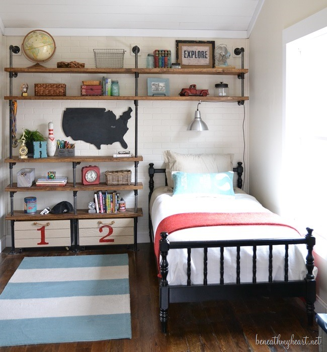 bedroom with twin bed, stripe rug, and map on wall